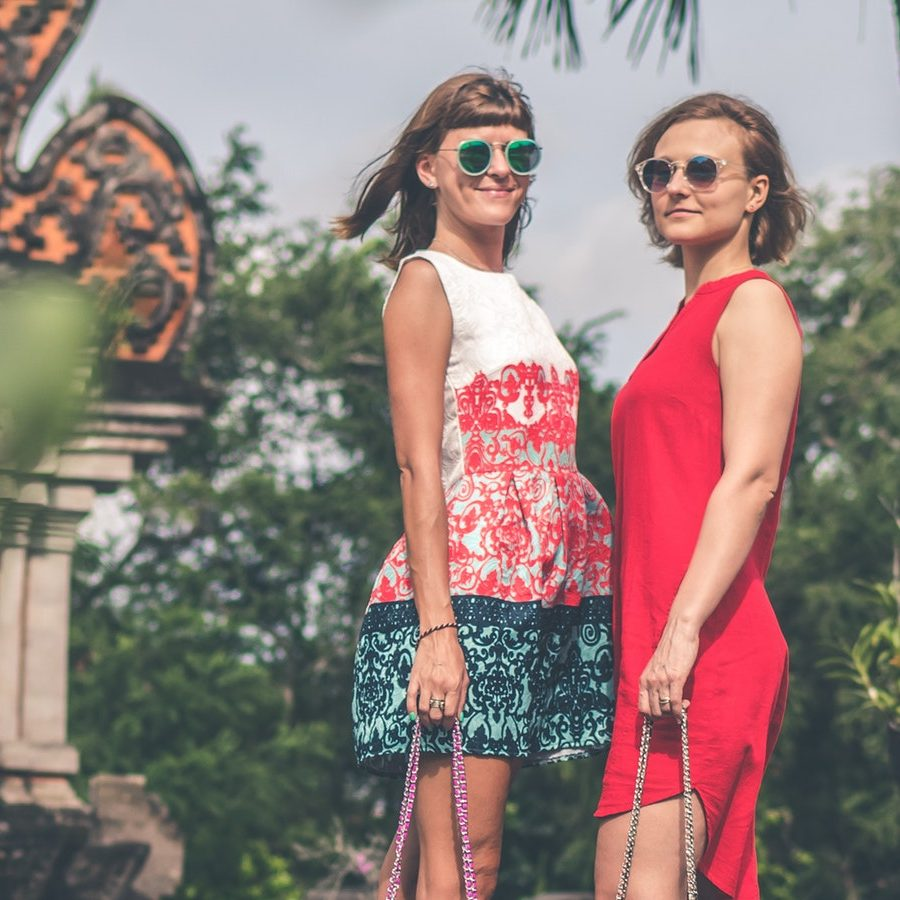 two-women-wearing-sunglasses-and-holding-bags-standing-on-1027077